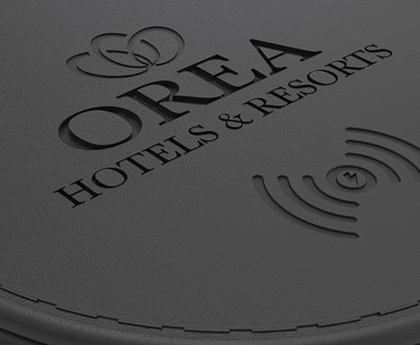 vyražené logo OREA na černé kuži qi nabíječky